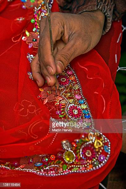 closeup of hand doing rich danka embroidery work on brightly colored fabric. thin polished golden shapes are secured using gold and silver wire. usually practiced by the men from the bohra community in udaipur. rajasthan, india. - indian bohra stock pictures, royalty-free photos & images
