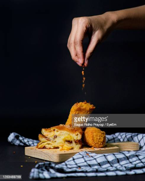 close-up of hand garnishing food served on table over black background - ready to eat stock pictures, royalty-free photos & images