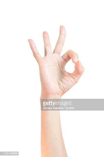 close-up of hand gesturing against white background - ok sign stock pictures, royalty-free photos & images