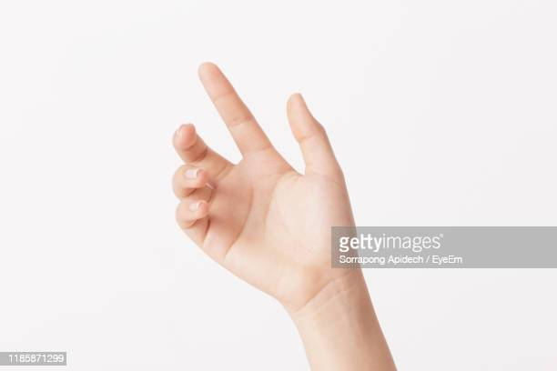 close-up of hand gesturing against white background - 親指 ストックフォトと画像
