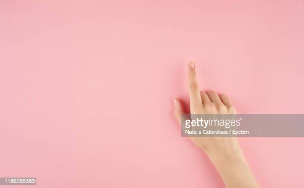 close-up of hand gesturing on pink background - menschlicher finger stock-fotos und bilder