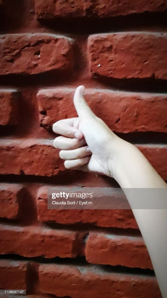 Close-Up Of Hand Gesturing Thumbs Up Against Brick Wall : Stock Photo
