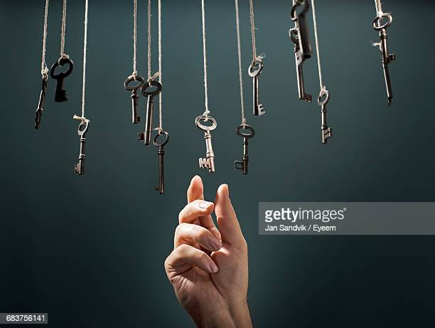 Close-Up Of Hand Hanging Against Black Background