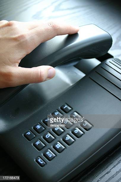 Close-up of hand hanging up a black phone