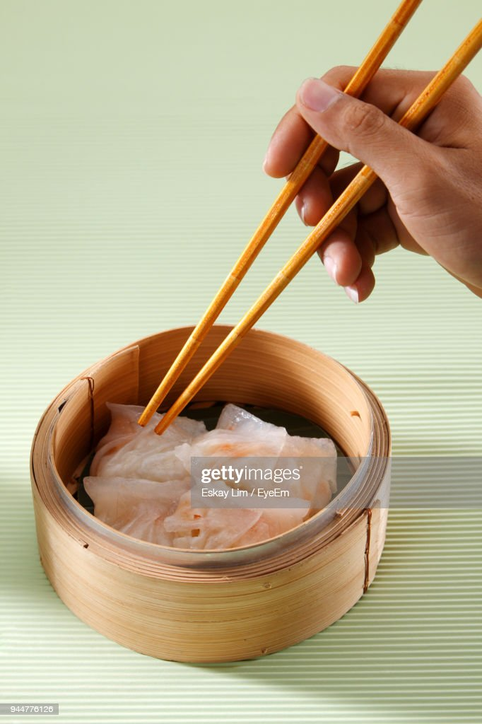 Close-Up Of Hand Having Dim Sum In Container With Chopsticks On Table : Stock Photo