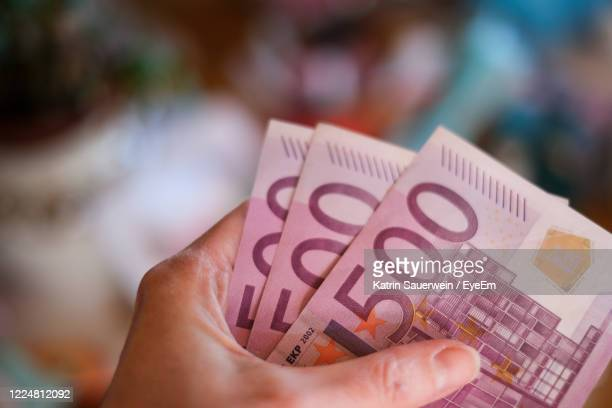 close-up of hand holding 500 euro banknotes - falsenews stock pictures, royalty-free photos & images
