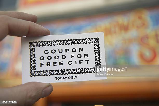 Closeup of hand holding a coupon for free gift at Coney Island