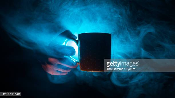 close-up of hand holding a cup against black background - back lit stock pictures, royalty-free photos & images