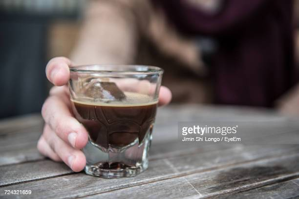 Close-Up Of Hand Holding A Glass Of Iced Coffee