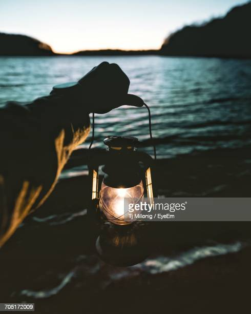 close-up of hand holding a lantern - oil lamp stock pictures, royalty-free photos & images
