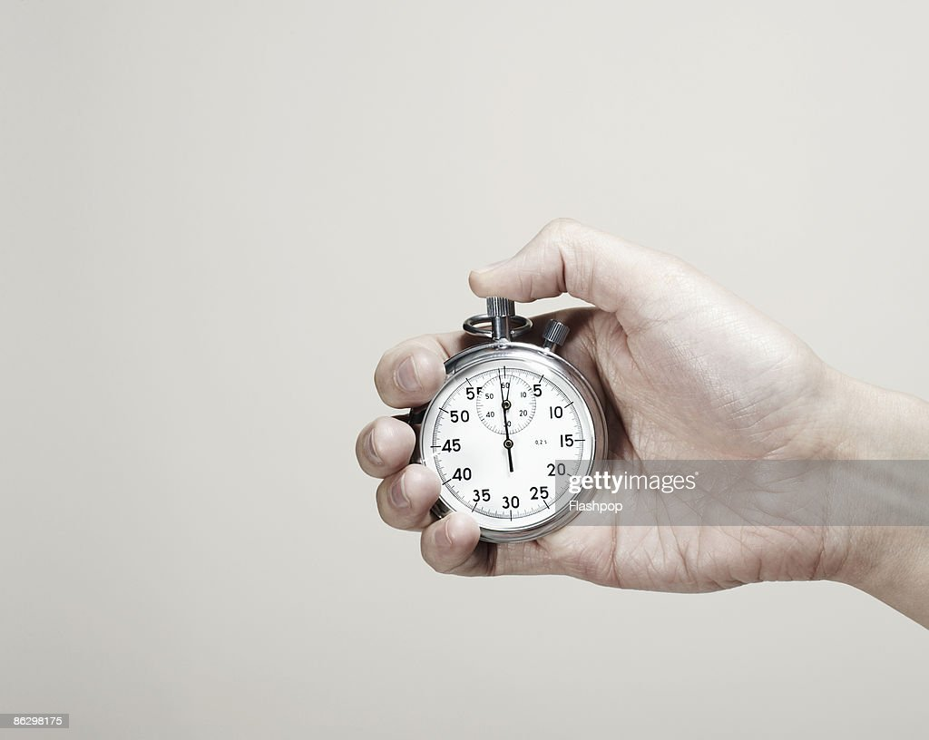 Close-up of hand holding a stopwatch  : Stock Photo