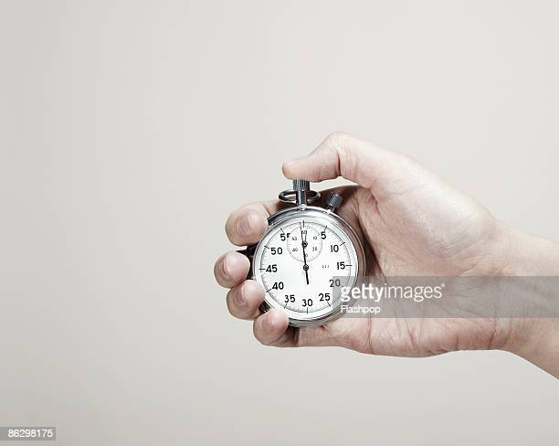 close-up of hand holding a stopwatch  - temps qui passe photos et images de collection