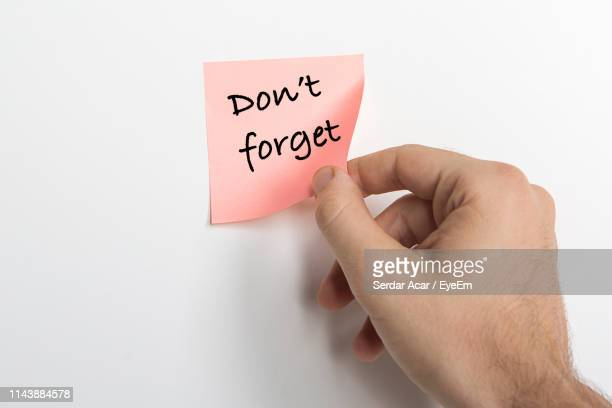 close-up of hand holding adhesive note with text against white background - reminder stock pictures, royalty-free photos & images