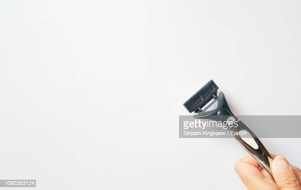 close-up of hand holding against white background - razor stock photos and pictures