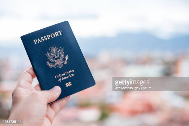 close-up of hand holding american passport against townscape - passeport photos et images de collection