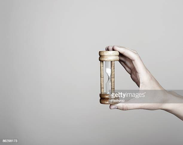 close-up of hand holding an egg timer - dringendheid stockfoto's en -beelden