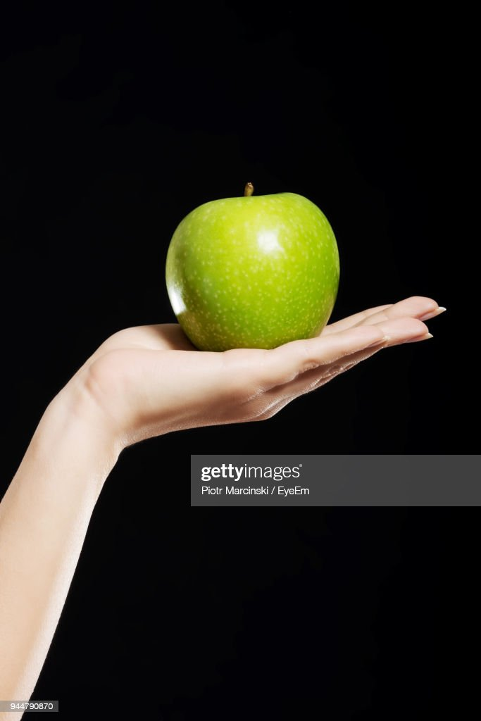Close-Up Of Hand Holding Apple Against Black Background : Stock Photo