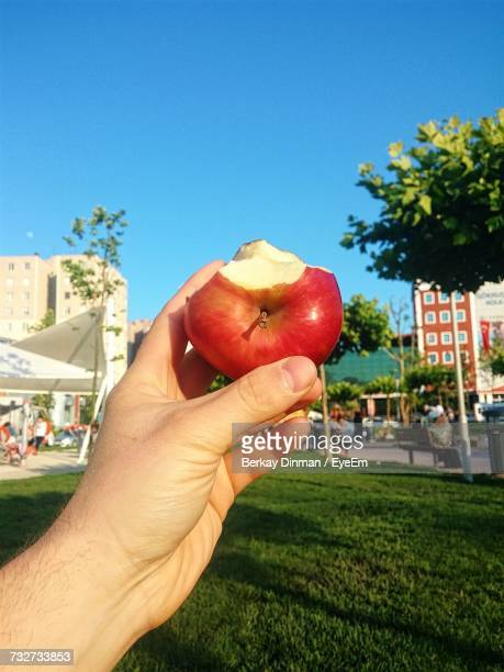 Close-Up Of Hand Holding Apple Against Clear Blue Sky