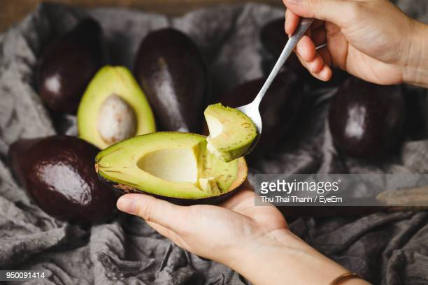 Close-Up Of Hand Holding Avocado