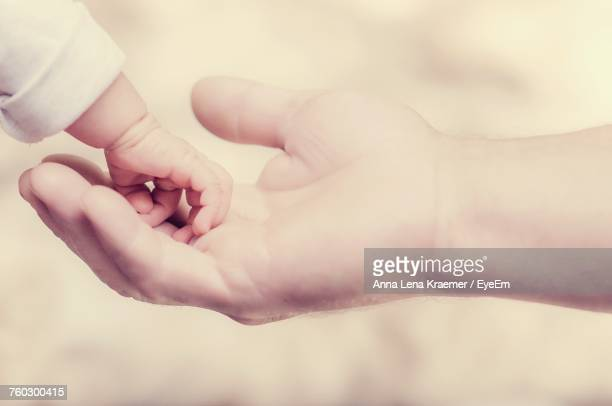 Close-Up Of Hand Holding Baby Hand