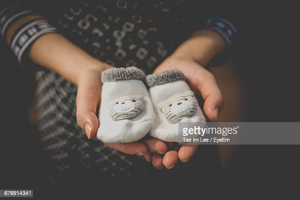 close-up of hand holding baby socks - baby booties stock photos and pictures