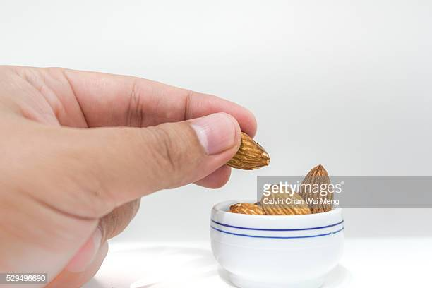 Close-up of hand holding baked almond nuts