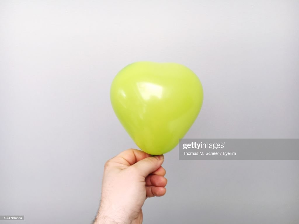 Close-Up Of Hand Holding Balloon Against Gray Background : Stock Photo