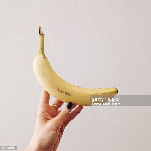 Close-Up Of Hand Holding Banana Over White Background