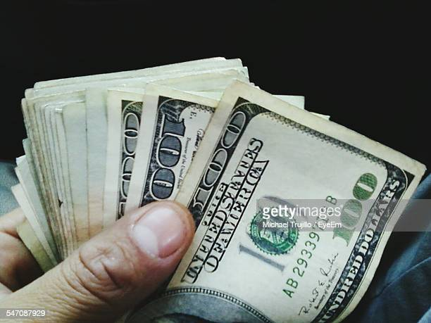 Close-Up Of Hand Holding Banknotes Over Black Background