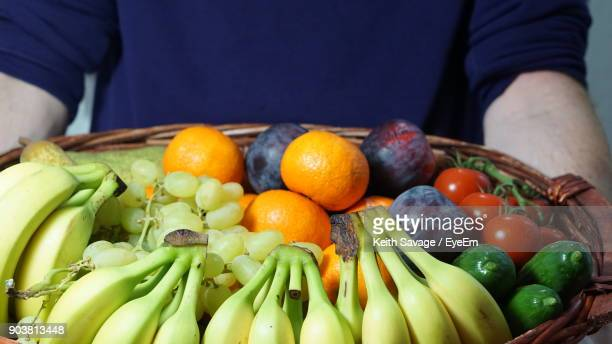 close-up of hand holding basket with fruits and vegetables - keith savage stock-fotos und bilder