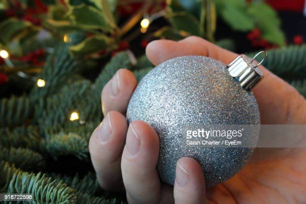 Close-Up Of Hand Holding Bauble Against Christmas Tree