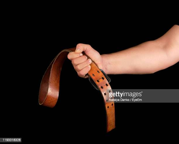 close-up of hand holding belt over black background - belt stock pictures, royalty-free photos & images