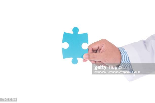 Close-Up Of Hand Holding Blue Puzzle