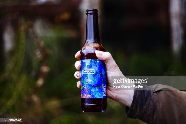 close-up of hand holding bottle - beer bottle stock pictures, royalty-free photos & images