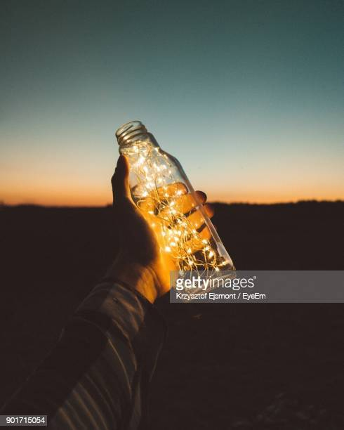 Close-Up Of Hand Holding Bottle With Illuminated String Light Against Clear Sky