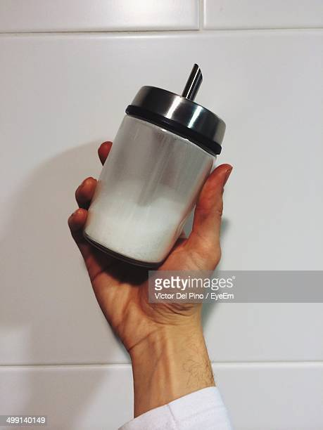 Close-up of hand holding bottle with milk against wall
