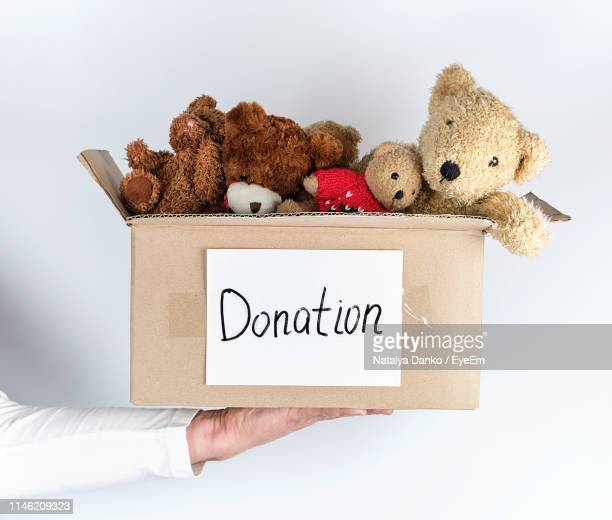 close-up of hand holding box of stuffed toy with text against white background - toy box stock pictures, royalty-free photos & images