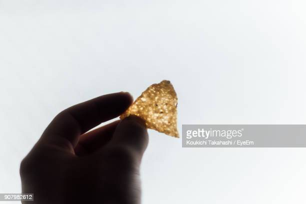 Close-Up Of Hand Holding Bread Against Clear Sky