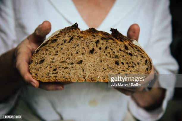 close-up of hand holding bread - germany stock pictures, royalty-free photos & images