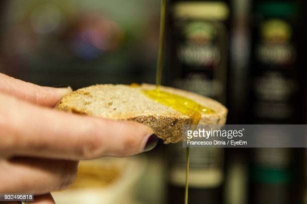 close-up of hand holding bread - olive oil stock pictures, royalty-free photos & images