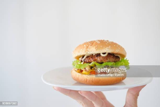 Close-Up Of Hand Holding Burger Against White Background