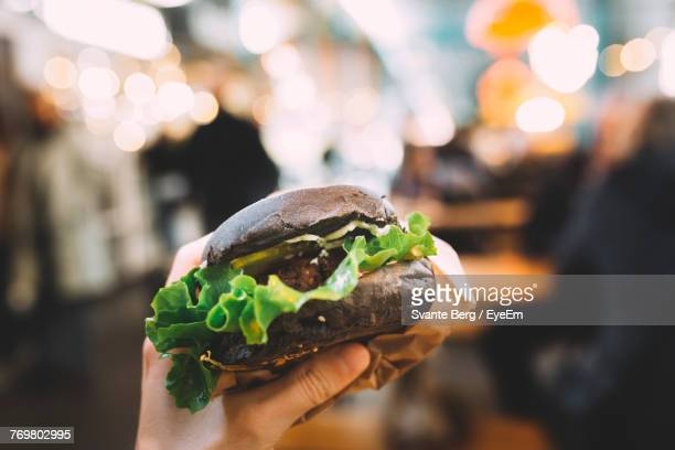 Close-Up Of Hand Holding Burger