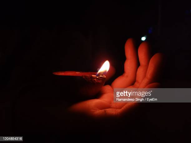 close-up of hand holding burning diya against black background - chandigarh stock pictures, royalty-free photos & images