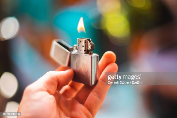close-up of hand holding burning lighter - cigarette lighter stock pictures, royalty-free photos & images
