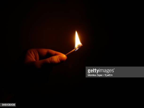Close-Up Of Hand Holding Burning Matchstick Against Black Background