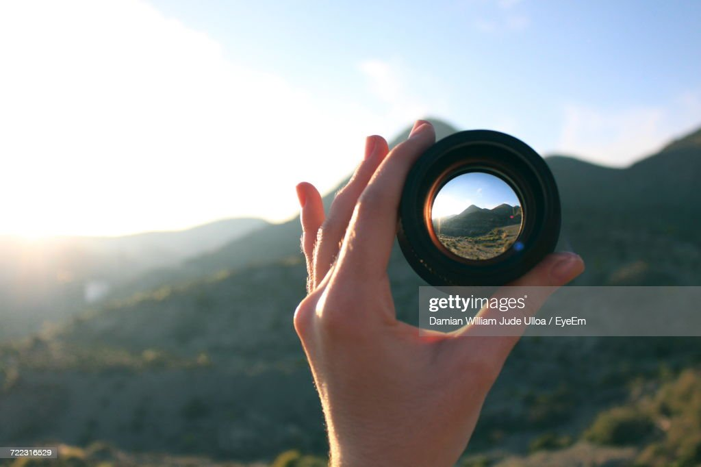 Close-Up Of Hand Holding Camera Lens Against Sky : Stock Photo