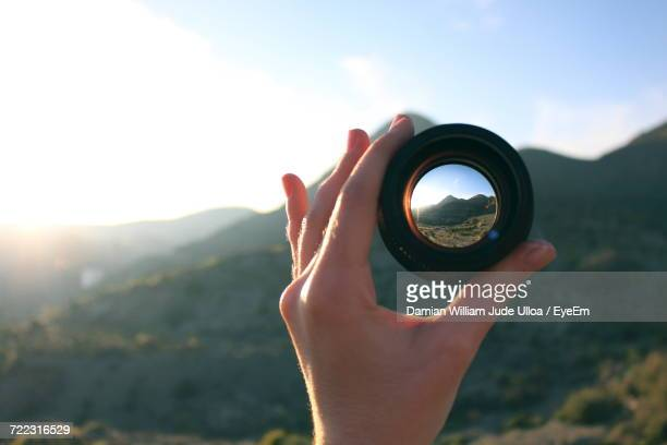 Close-Up Of Hand Holding Camera Lens Against Sky