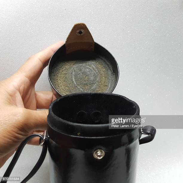 close-up of hand holding camera lens case against gray background - strap stock pictures, royalty-free photos & images
