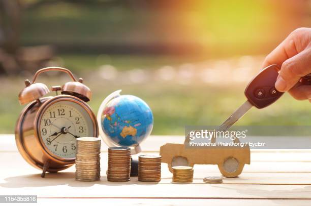 close-up of hand holding car key by coins and globe with alarm clock on table - car alarm stock photos and pictures