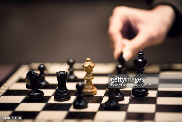 close-up of hand holding chess piece - reality kings stock pictures, royalty-free photos & images